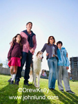 Photo of a family walking their hound dog in the park. Four family members, mom, dad, and a boy and a girl.